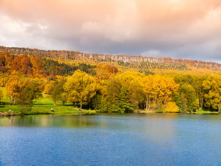 czech switzerland: Sandstone rock formation in the middle of colorful autumn forest. Water surface on the foreground. Dramatic evening view. Tisa Rocks, aka Tiske Walls, Czech-Saxon Switzerland, Czech Republic