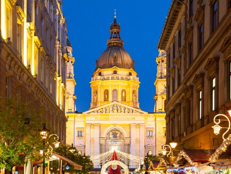 Christmas time in Budapest. Illuminated dome of Saint Stephen's Basilica with holiday street decoration in Zrinyi Street by night. Hungary, Europe. Stok Fotoğraf