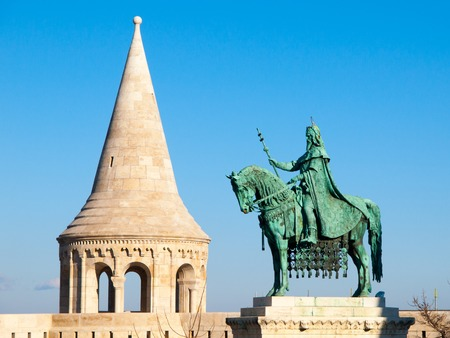 bastion: Mounted statue of Saint Stephen I, aka Szent Istvan kiraly - the first king of Hungary at typical white rounded tower of Fishermans Bastion in Buda Castle in Budapest, Hungary, Europe. Sunny day shot with blue sky on the background.