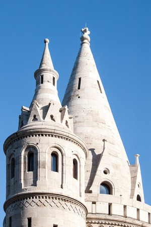 halaszbastya: Typical light stone rounded fairy tale towers of Fishermans Bastion, aka Halaszbastya, on a terrace in neo-Gothic and neo-Romanesque architectural style. Lookout turrets are situated on a Buda bank side of Danube River in Budapest, capital city of Hungar