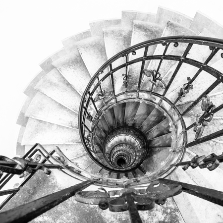 Upside view of indoor spiral winding staircase with black metal ornamental handrail. Architectural detail in St. Stephens Basilica in Budapest, Hungary. Black and white image.