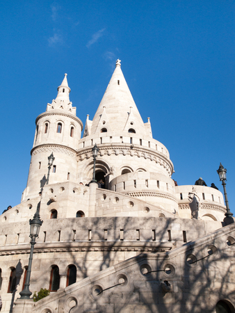 bastion: Typical light stone rounded fairy tale towers of Fishermans Bastion, aka Halaszbastya, on a terrace in neo-Gothic and neo-Romanesque architectural style. Lookout turrets are situated on a Buda bank side of Danube River in Budapest, capital city of Hungar