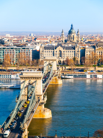 Famous Chain Bridge over Danube River, Gresham Palace and Saint Stephens Basilica view from Buda Castle on sunny autumn day in Budapest, capital city of Hungary, Europe. UNESCO World Heritage Site