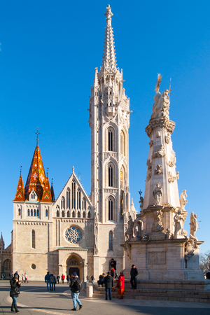 central european: Roman Catholic Matthias Church and Holy Trinity plague column at Fishermans Bastion in Buda District, Budapest, Hungary, Europe. Sunny day shot with clear blue sky.