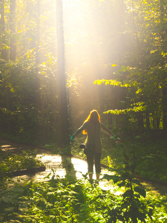 Faithful woman thanking god with open arms in nature illuminated by bright light shining from heaven. Praying and faith concept.