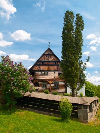 The Dlaskuv statek Farm - old timbered building typical for Jizera region, Dolanky Village near Turnov in Bohemian Paradise, Czech Republic, Europe. Sunny summer day shot with blue sky. Stock Photo