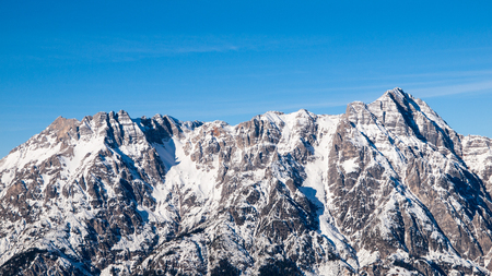 High rocky snowy peak on sunny winter day with blue sky. Alpine mountain ridge.