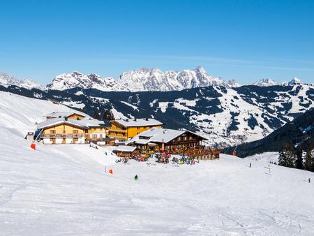 Downhill slope and apres ski mountain hut with restaurant terrace in Saalbach Hinterglemm Leogang winter resort, Tirol, Austria, Europe. Sunny day shot.