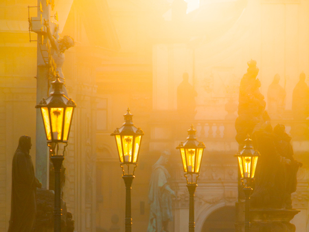 Street lamps on Charles bridge illuminated by sun in the morning, Old Town, Prague, Czech Republic.