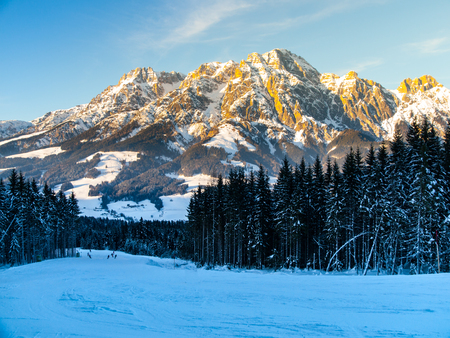 Downhill slope in Saalbach Hinterglemm Leogang winter resort, Tirol, Austria, Europe. Sunny morning with clear sky and illuminated mountain massive on the background. Stock Photo