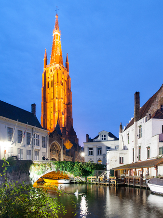 Church of Our Lady and bridge over water canal by night, Bruges, Belgium. Stock Photo