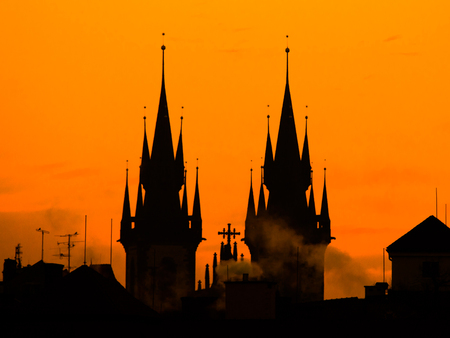Silhouette of two towers of Church of Our Lady before Tyn in morning Prague, Czech Republic. Contrast black controur and orange sky.
