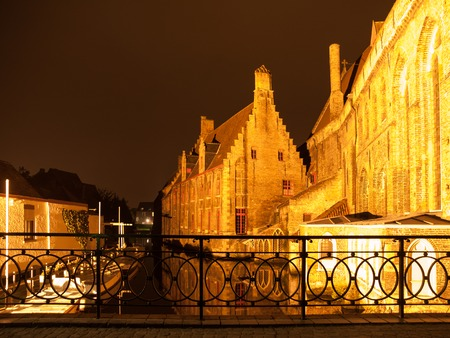 Water canal at Old Saint Johns Hospital by night, Bruges, Belgium.