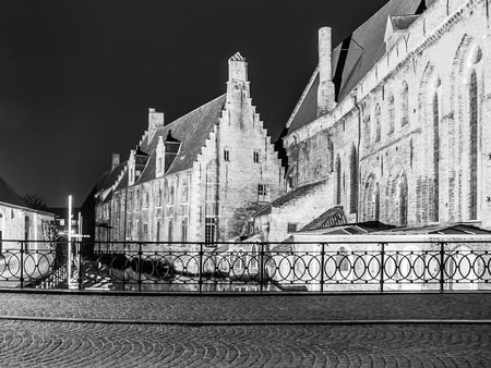 Water canal at Old Saint Johns Hospital by night, Bruges, Belgium. Black and white image.