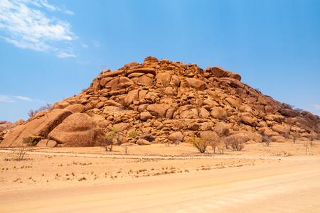 Orange rock formation in dry desert landscape near Twyfelfontein in Damaraland, Namibia.