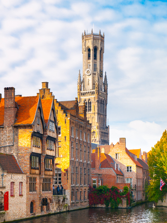 Belfry Tower and brick houses at water canal, Bruges, Belgium. HDR image. Stock Photo