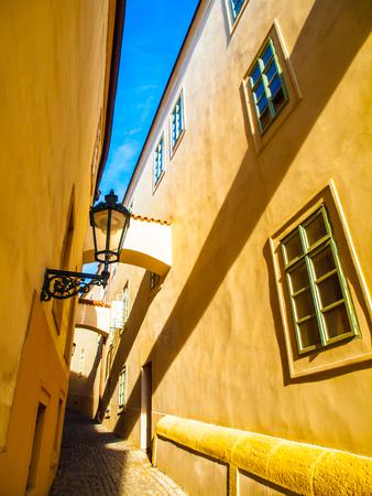 archways: Morning Prague scene. Sunlit and long shadows on the wall with gas street lamp, Thunovska Street, Lesser Town, Prague, Czech Republic.