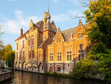 Old brick houses along water canals in Bruges, Belgium.