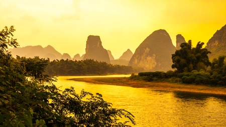 Sunset panorama in karst landscape around Yangshuo an Li River with peaks silhouettes, Guangxi Province, China.