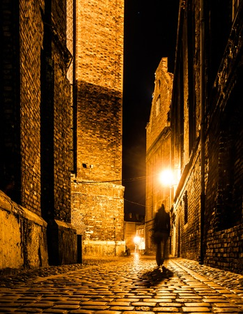 Cobbled street of Old Town with dark blurred silhouette of person. Evokes Jack the Ripper. 免版税图像 - 96148404
