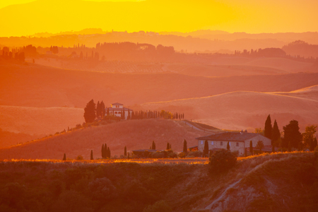 Evening in Tuscany. Hilly Tuscan landscape in golden mood at sunset time with silhouettes of cypresses and farm houses near Volterra, Italy.