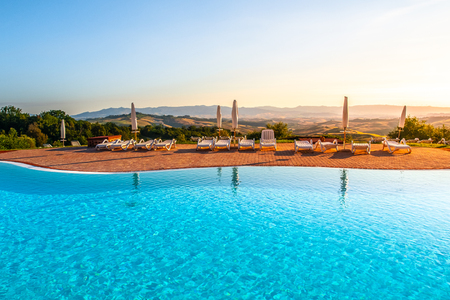 Beautiful luxury swimming pool with bright blue water, umbrellas and sunbeds in Tuscan landscape. Evening summer sunset. Italy. Archivio Fotografico