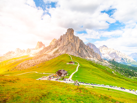 Landscape of Dolomites with green meadows, blue sky, white clouds and rocky mountains.