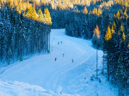 People on ski slope in mountain resort on sunny winter morning.