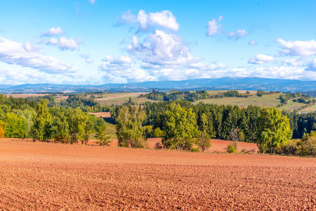 Typical red soil of countryside around Nova Paka. Agricultural Landscape with Giant Mountains on the background. Czech Republic. Фото со стока