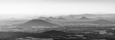 Silhouettes of volcanic hills of Ceske Stredohori, Central Bohemian Uplands, on sunny and hazy day. Czech Republic. Black and white image.