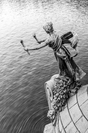 Torch bearer woman figure - bronze decoration of Svatopluk Cech Bridge over Vltava River in Prague, Czech Republic. Black and white image. Фото со стока