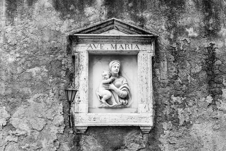 Street wall religious niche with small sculpture of Maria with Jesus. Black and white image. Stockfoto - 123168273
