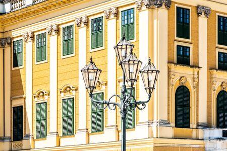 VIENNA, AUSTRIA - 23 JULY, 2019: Schonbrunn Palace, German: Schloss Schonbrun, baroque summer residence of Habsburg monarchs in Hietzing, Vienna, Austria. Detailed view of facade and ornamental street lamp.