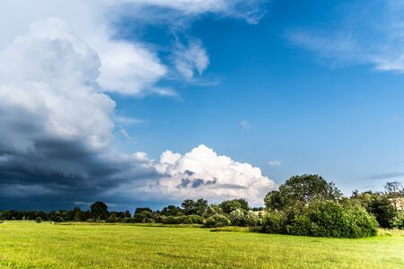 Before summer storm. Dramatic clouds coming in green and sunny landscape.