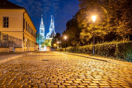 Church of St. Peter and Paul on Vysehrad. Cobbled street by night. Prague, Czech Republic.