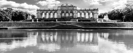 VIENNA, AUSTRIA - 23 JULY, 2019: The Gloriette in Schonbrunn Palace Gardens, Vienna, Austria. Front view and water reflection. Black and white image.
