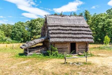 Small shepherd hut with straw roof on sunny day. Stock Photo