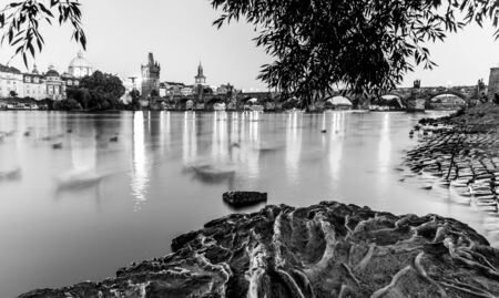 Vltava River and illuminated Charles Bridge at evening time. Prague, Czech Republic. Black and white image.