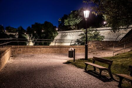 Walkway on Vysehrad fortification walls illuminated by street lamps by night. Prague, Czech Republic.