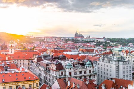 Evening sunset in Prague. Prague Castle illuminated by sun flare, Czech Republic. View from Old Town Hall Tower. Imagens