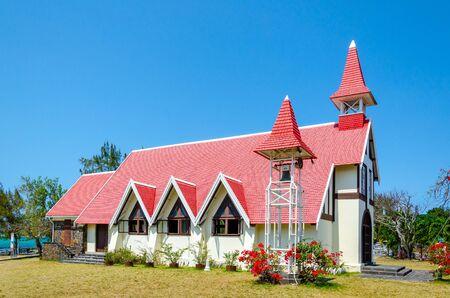 Notre Dame de Auxiliatrice - wiejski kościół z czerwonym dachem w tropikalnej wiosce Cap Malheureux na wyspie Mauritius, Ocean Indyjski. Zdjęcie Seryjne