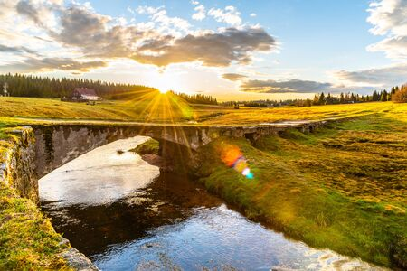 Rural landscape with stream and stone bridge in sunny spring evening. Sunset in Jizerka village with Jizerka river, Jizera Mountains, Czech Republic.