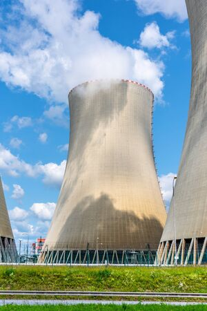 Cooling towers of nuclear power plant. On sunny day with blue sky and white clouds.