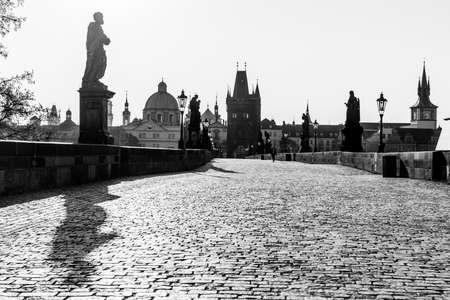 Morning on Charles Bridge, Czech: Karluv most. Hazy sunrise daybreak. Praha, Czech Republic. Black and white image.