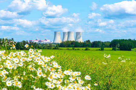 Nuclear power plant on the background of beautiful green and blooming summer meadow. Temelin, Czech Republic.