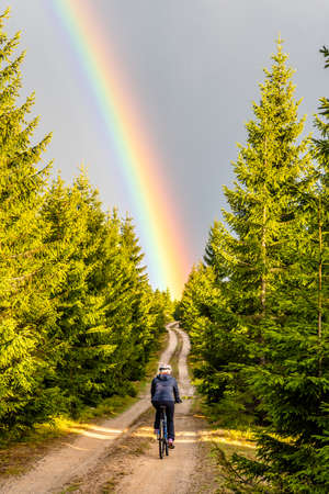 Mountain bike cycling after rain. Woman rides towards bright rainbow through forest country road. Outdoor sport theme.