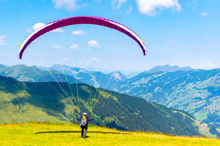 Paraglide launching. Starting procedure of paraglider on high mountain meadow. Recreational and competitive adventure sport. Banque d'images