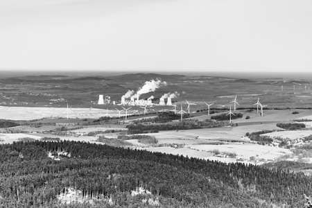 View of wind turbines near Hradek nad Nisou, Czech Republic, in contrast to coal power plant Turow, Bogatynia, Poland. Place of international conflict over the expansion of power station. Black and white image.