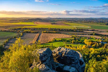 Autumn hilly landscape at sunset time. Colorful trees and meadows. View of Krkonose, Cisarsky kamen and Cerna Studnice, Czech Republic Reklamní fotografie