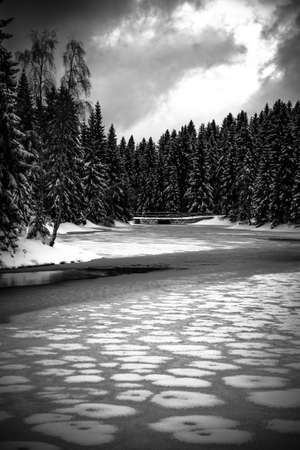 Icy winter at frozen pond. Snowy landscape. Blatny Water Reservoir in Jizera Mountains, Czech Republic Black and white image.
